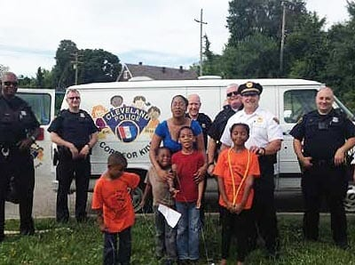 Officers and children by Cops for Kids truck