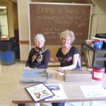 Committee members Marcia Nolan and Rose Roy helping at the event