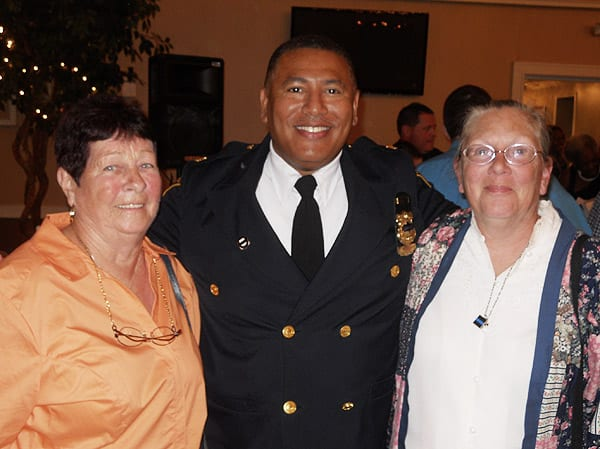Commander Deon McCaulley welcomes long time Fourth District residents Betty Rodes (on left), and Linda Lewis  (on right) to the ceremony.