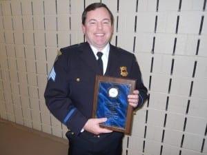Sgt. Bryan Curry displays Burt Saltman's Award. (Burt was unable to attend)