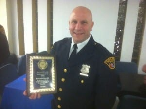 Detective Michael Kitchen #1316 holding his Community Service Award