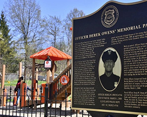 A sign covering Officer Derek Owens' life and service in front of the playground at Derek Owens Memorial Park
