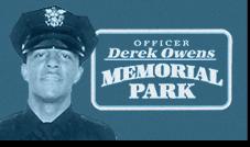 A photo of Officer Derek Owens in front of a sign for the Officer Derek Owens Memorial Park